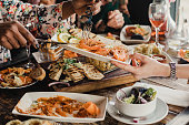 Point of view image of a group of multi-ethnic friends sharing multiple dishes, with a plate of prawns as the main focus.