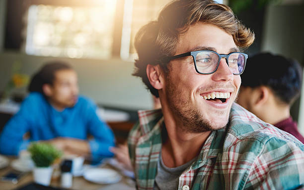 Sharing laughs over coffee Shot of a smiling young man sitting at a cafe table with friends in the background adult student stock pictures, royalty-free photos & images