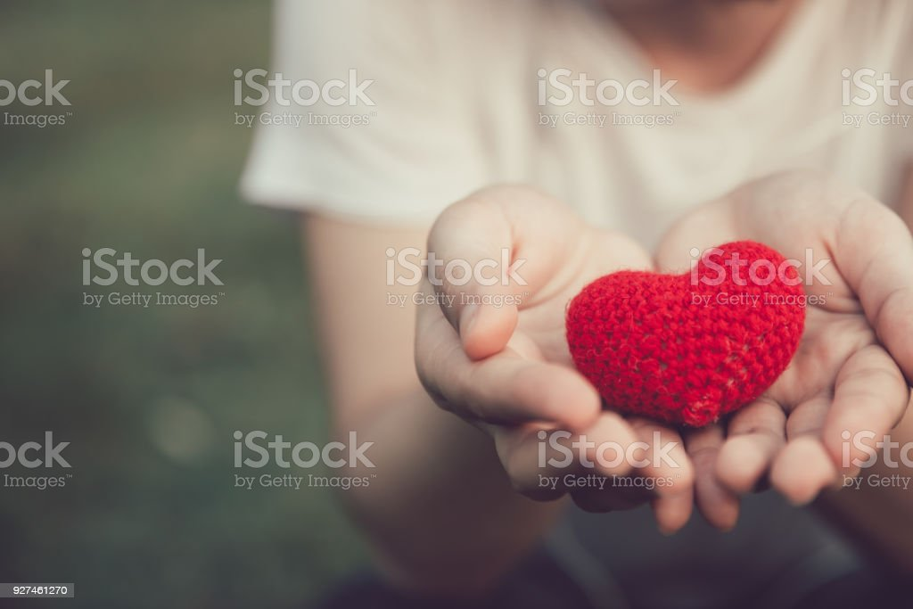 Sharing Love and Heart red color on women hand in valentine's day vintage color tone stock photo