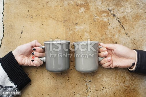 Two women holding hot coffee and chocolate grey mug, cheer up and drinking together with brown wall.