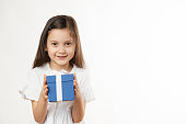 Front view of a cute little girl is holding a blue gift box in her hands with a nice smile in front of pure white background.