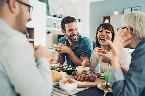 Group of friends gathered around the table with food and drinks, having good time together