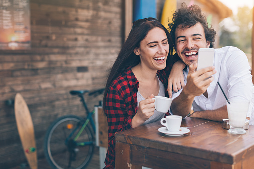 Young woman and man drinking coffee and looking at a smart phone outdoors in the summer, with copy space.