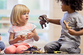 A multi-ethnic group of elementary age children are playing together with plastic animal toys at day care.