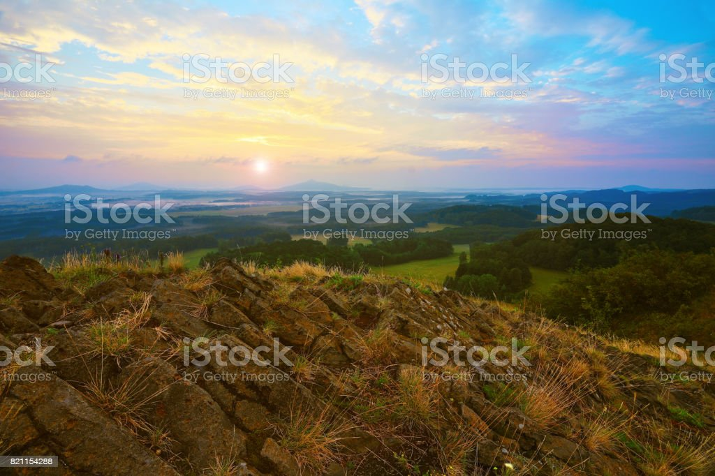 Sharp cliffs. Rocky basalt peak on hill. Forest valley  and Sun above horizon. stock photo