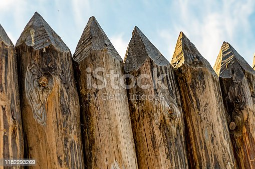 sharp logs row of pointed trunks the base of a wooden fence stands against the sky