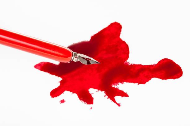 scharfe feder in rotem dip-stift über rotem farbfleck - dip gefärbt stock-fotos und bilder