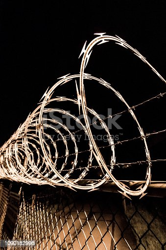 Razor wire fence, keep out, no trespassing. Sharp, scary, chainlink fence. Night, detailed. Security, protection, prison