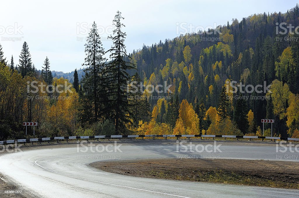 Sharp road bend in autumn forest stock photo