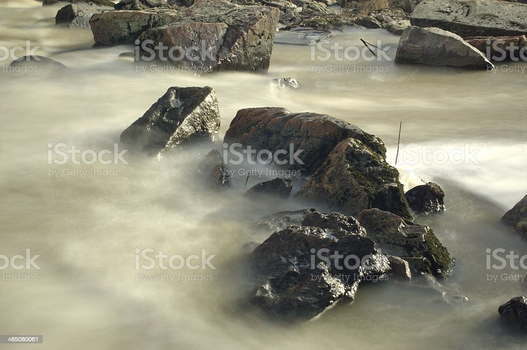 Sharp rocks in softly flowing river stock photo