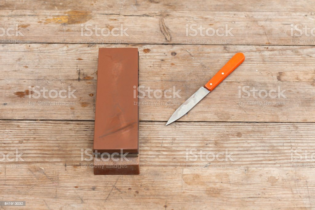 Sharp sharpen knife with grindstone stock photo