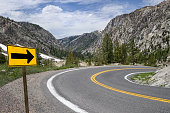 A sign points the way along a winding road through the Sierra Nevada Mountains.