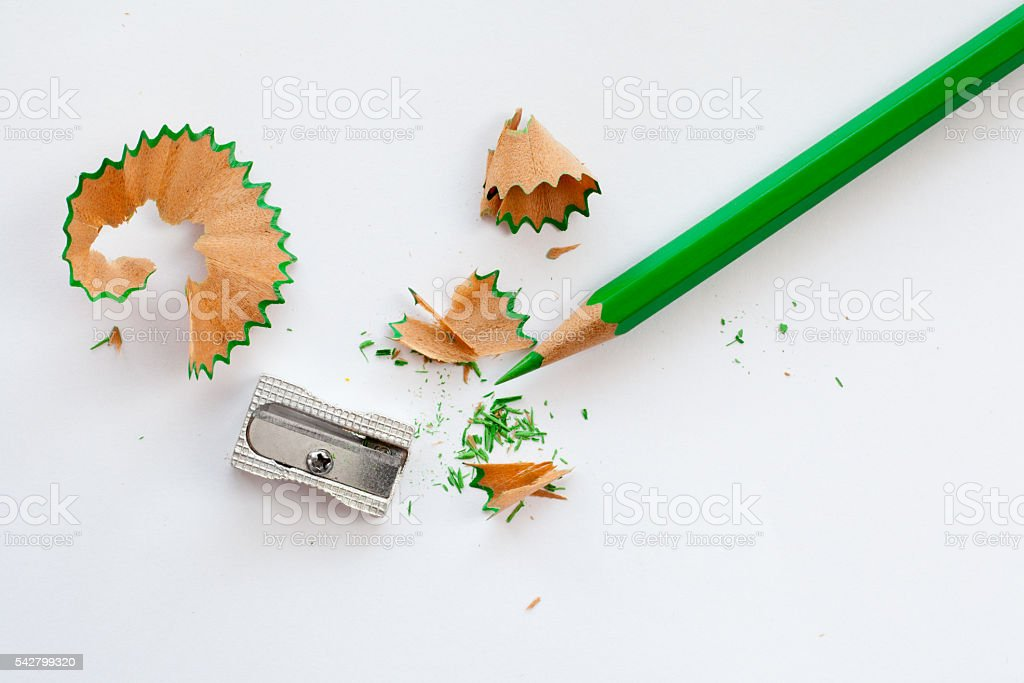 sharpener, green wooden pencil and pencil shavings on white
