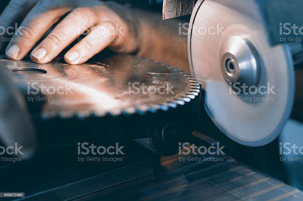 Sharpening Circular Saw, worker sharpens a circular saw blade stock photo