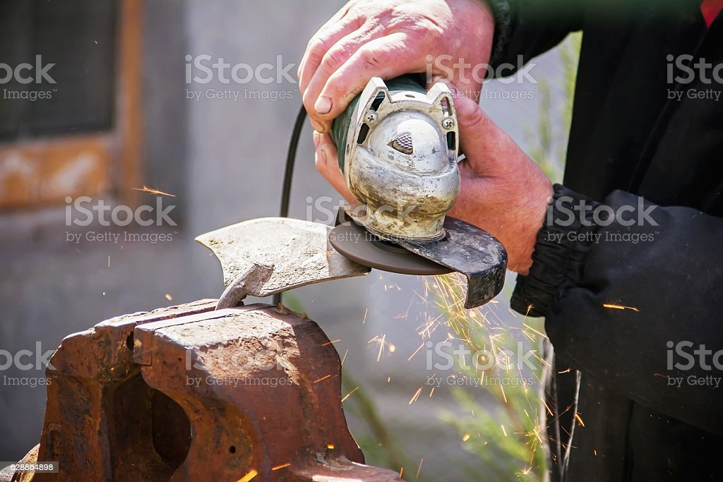 sharpening garden tools hoe using grinder close-up, Machine for stock photo