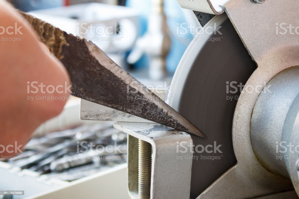 Sharpening knife of a shoemaker on grinding machines stock photo
