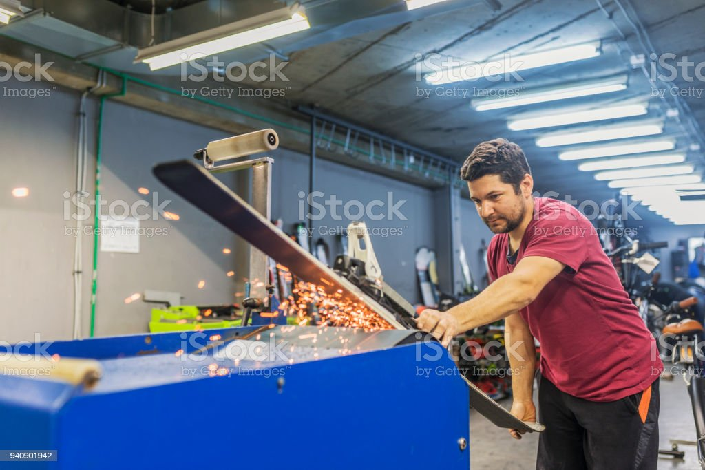 Sharpening of an edging of mountain skis, Grinding and sparks stock photo