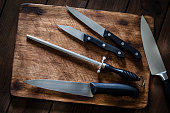 istock Sharpening steel and various kitchen knives on wooden cutting board 1066533044