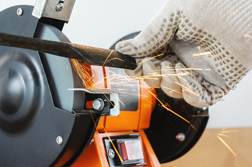 Sharpening the blade of a lawn mower with an electric sharpener. Hands in work gloves hold and sharpen the blade.
