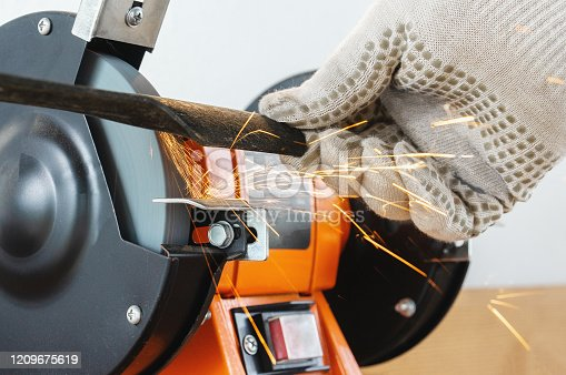 istock Sharpening the blade of a lawn mower with an electric sharpener. Hands in work gloves hold and sharpen the blade 1209675619