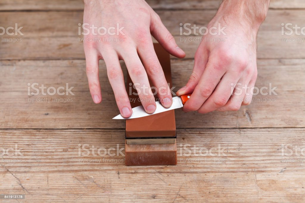 Sharpening the knife with a whetstone on a wooden background. Top view stock photo