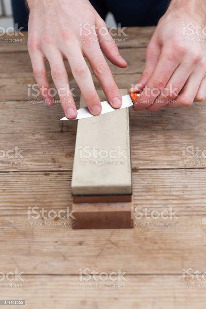 Sharpening the knife with a whetstone on a wooden background. Top view. stock photo