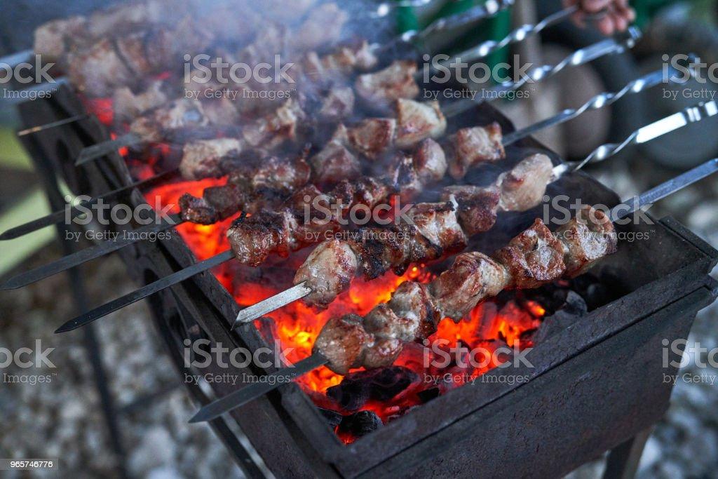 Sjasliek voorbereiden op een barbecue-grill op houtskool. Stukken vlees op een spies. Shish kebab bereiden in brand. - Royalty-free Buitenopname Stockfoto