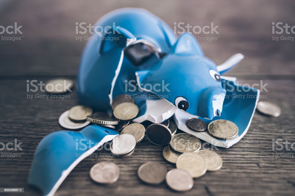 shattered broken piggy bank with coins on rustic wooden table stock photo
