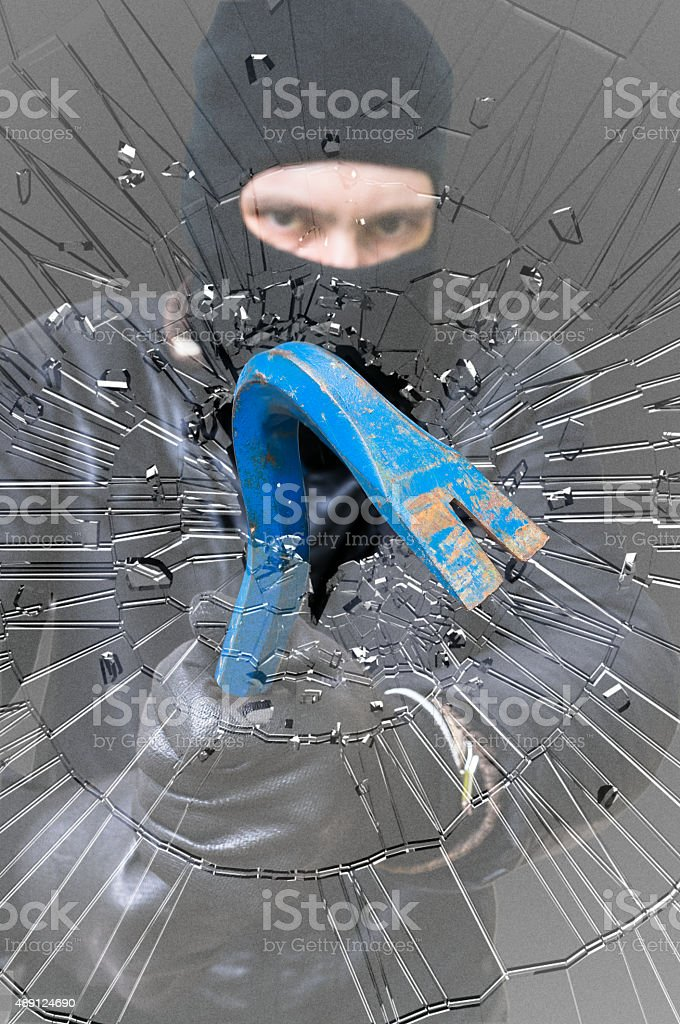 Shattered glass. Burglar or thief masked with balaclava stock photo
