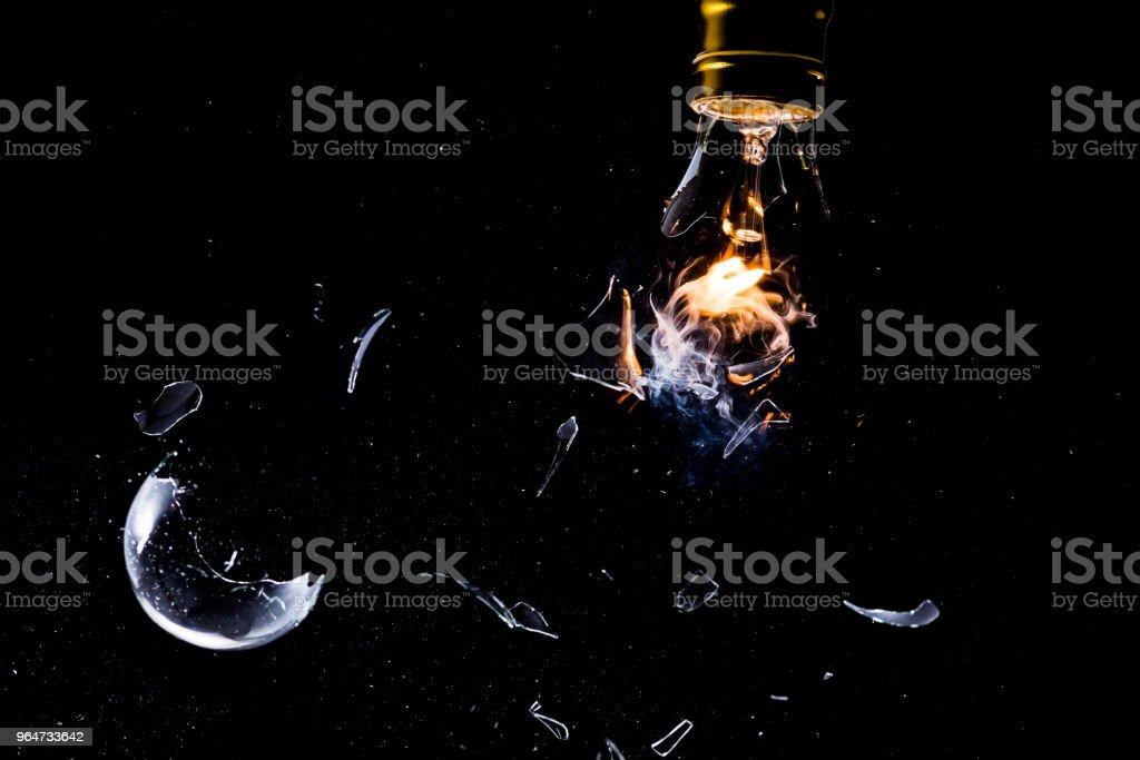 A shattering Lit Lightbulb stock photo