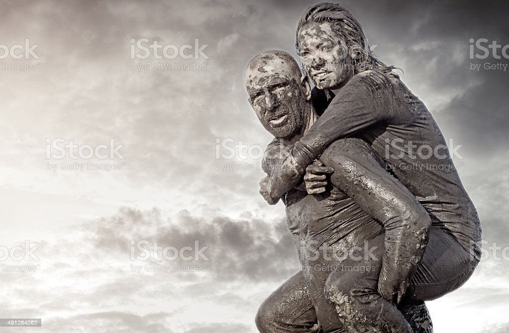 Shaved man carrying female friend during a mud run stock photo