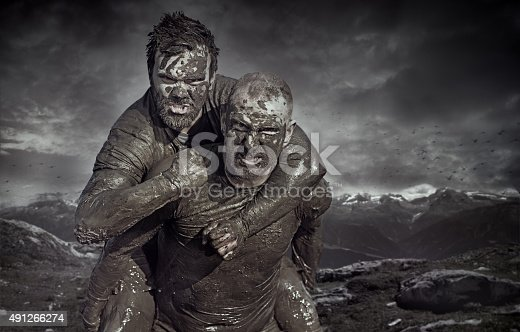 istock Shaved man carrying friend during a mud run 491266274