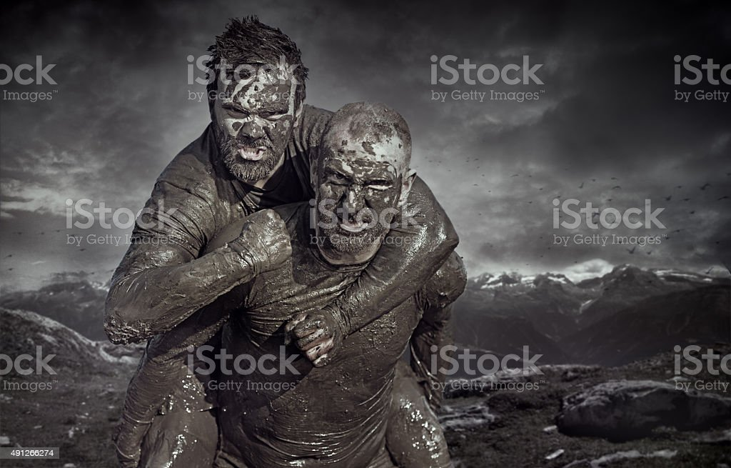 Shaved man carrying friend during a mud run stock photo