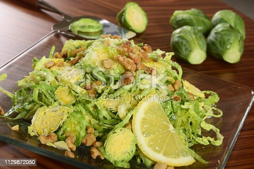 Healthy shaved raw brussels sprout salad with toasted walnuts and parmesan cheese.