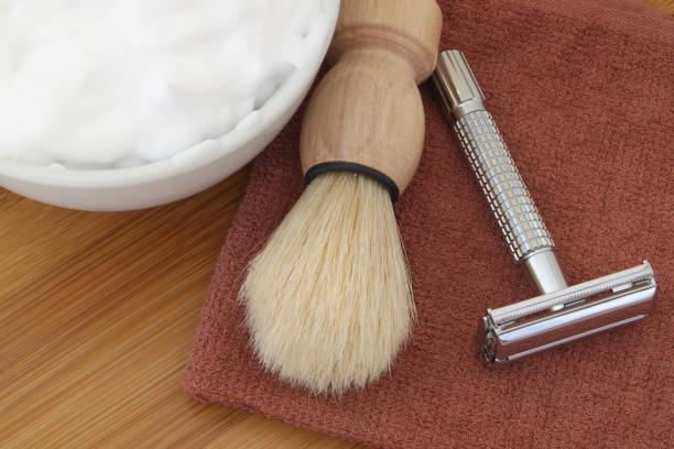 Shaving accessories on wooden background. Shaving accessories on wooden background. Razor, brush, towel and foam in bowl. shaving brush shaving cream razor old fashioned stock pictures, royalty-free photos & images