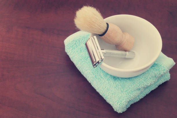 Shaving accessories on wooden background. Shaving accessories on wooden background. Razor, brush and towel with bowl. shaving brush shaving cream razor old fashioned stock pictures, royalty-free photos & images
