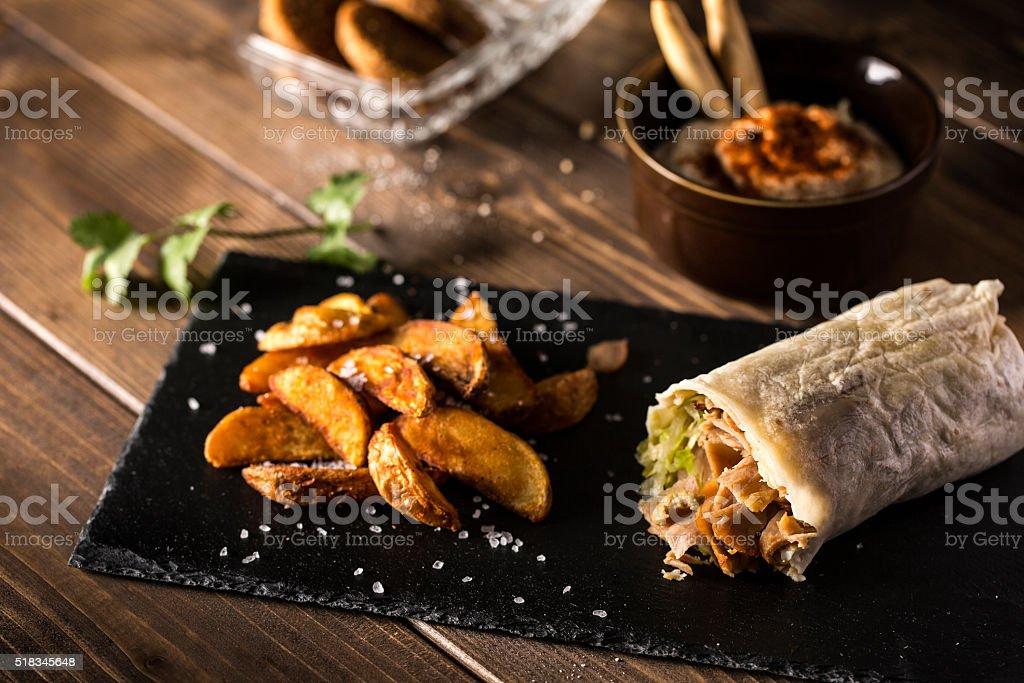 Shawarma with fried potato on table stock photo