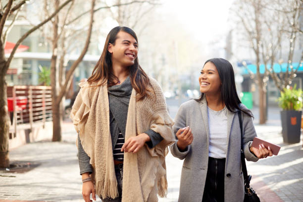 She always has juicy stories to tell Cropped shot of two affectionate young friends having a discussion while walking in the city transgender stock pictures, royalty-free photos & images