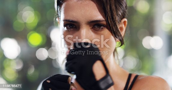 Cropped portrait of an attractive young female kickboxer training in the gym