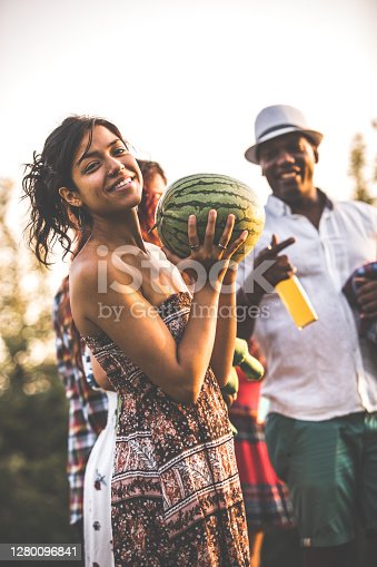 Three quarter length of a woman in off shoulder dress carrying a green watermelon for a summer picnic with her friends. She smiles happily towards the camera.