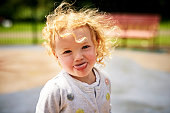 Portrait of an adorable little girl sticking her tongue out outdoors