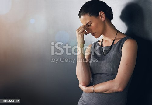 Studio shot of a businesswoman looking stressed out against a grey background