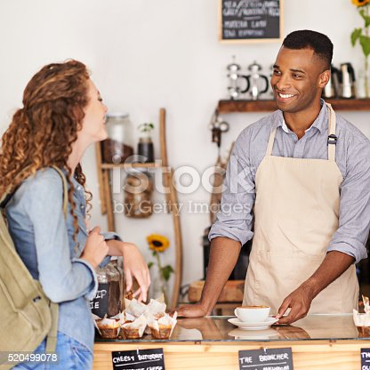 Shot of young barista serving a customer a cup of coffee at a cafe