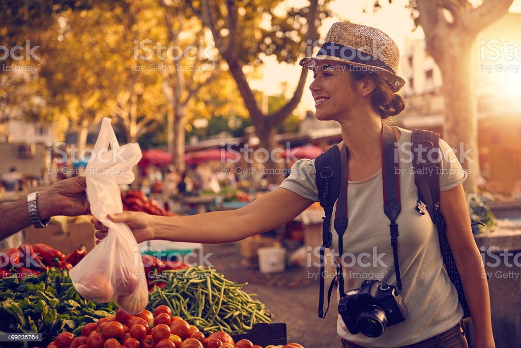 Shot of a woman buying fruit and vegetables at a market in a foreign...