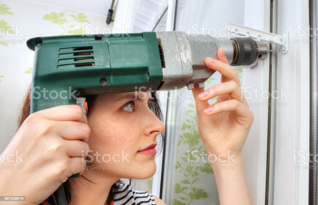She does fixing holes for window limiter using an drill. stock photo