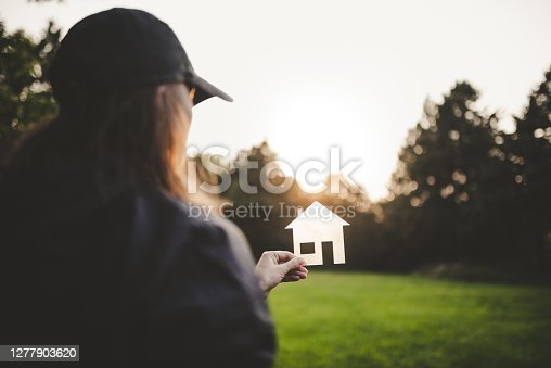 Woman in green field holding transparent house symbol against the sun. Real estate, housing, mortgage, construction industry, architecture and design concept.