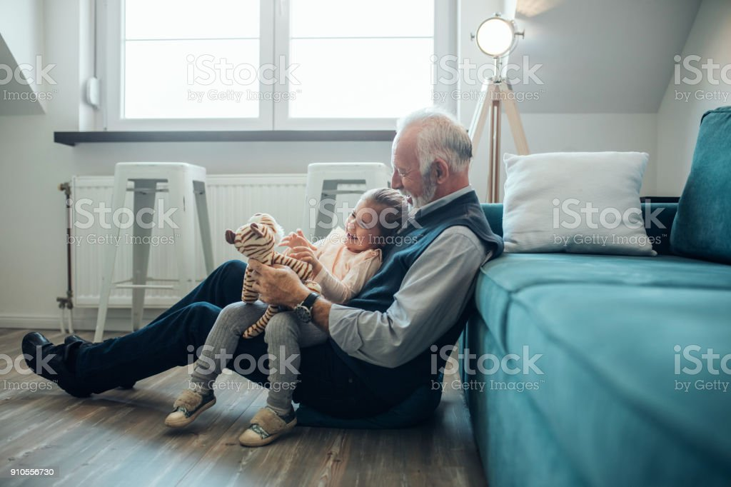 She enjoys grandpa's jokes stock photo