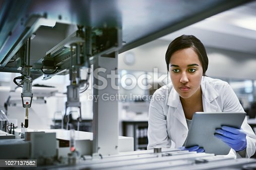 Shot of a young woman using a digital tablet while working in a laboratory