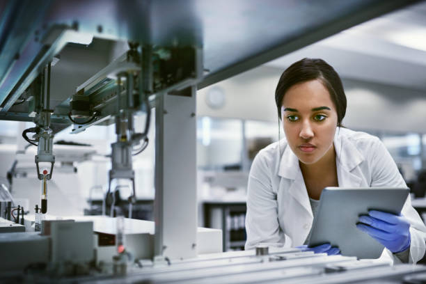 She finds the answers to life's mysteries Shot of a young woman using a digital tablet while working in a laboratory biochemist stock pictures, royalty-free photos & images