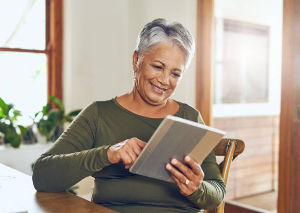 She gets all her news online Shot of a mature woman using a digital tablet at home one mature woman only stock pictures, royalty-free photos & images